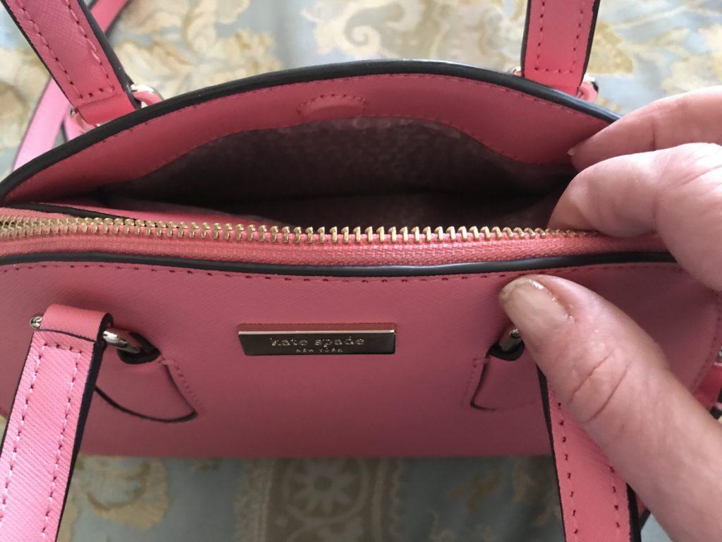 Porte-monnaie Kate Spade Reiley montrant la pochette à l'extérieur qui se ferme à l'aide d'une fermeture magnétique, neversaydiebeauty.com