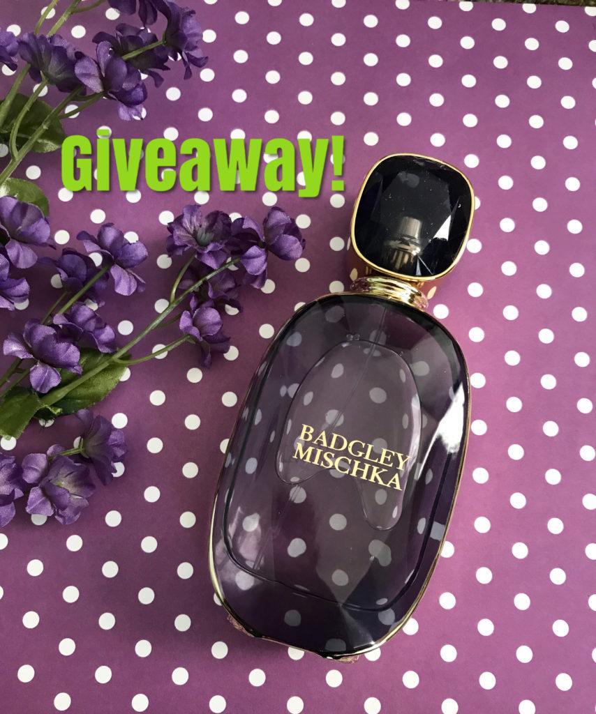 bouteille en verre mauve à facettes de l'Eau de Parfum Badgley Mischka avec un cadeau indiqué sur la photo, neversaydiebeauty.com
