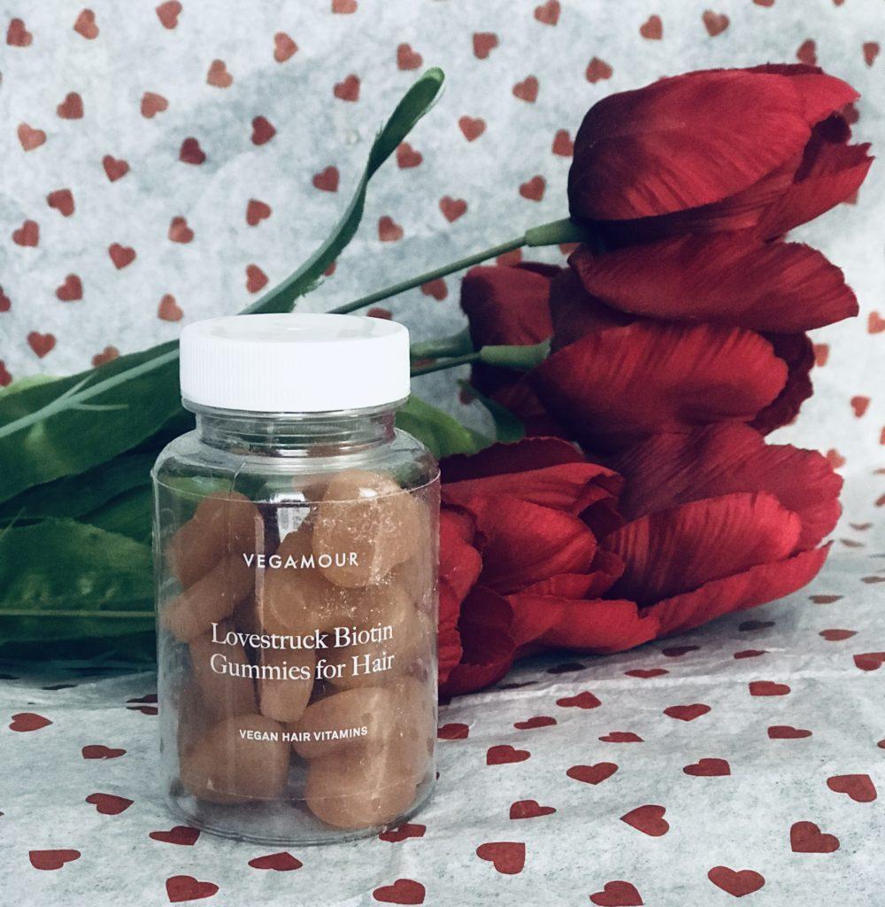 Bouteille en plastique transparent de Vegamour Lovestruck Biotin Gummies for Hair sur fond de papier blanc avec des coeurs rouges et des tulipes rouges