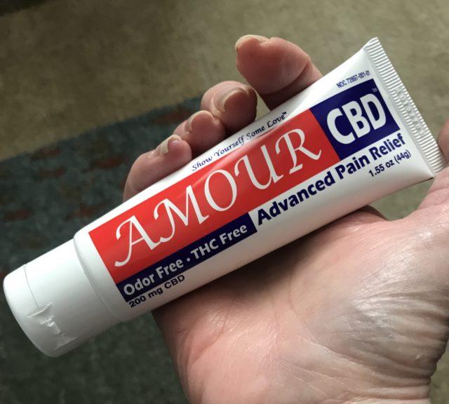 ma main tenant un tube d'Amour CBD Advanced Pain Relief Cream pour que vous puissiez voir la taille du tube